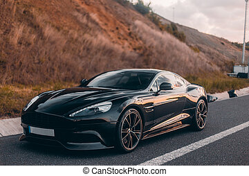 Black sport cabriolet on the mountain road