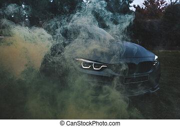 Black sport car under the steam effect