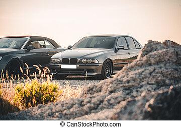 Black sport sedans parking on the hill