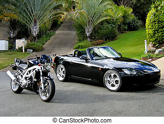 Black sportscar and sportsbike pictured together against a tropical garden background