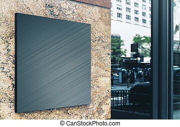 Black square sign with blank space for your logo on the marble wall of a modern business center, mockup