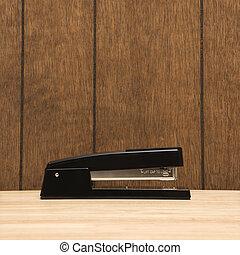 Black stapler on desk with wooden paneling.