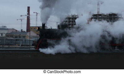 steam train in clouds of smoke and steam passes by