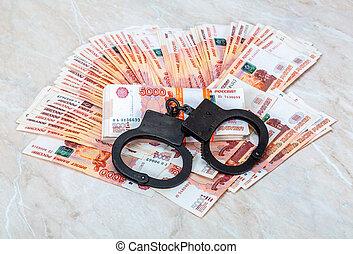 Black steel handcuffs lying on the heap of money