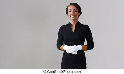Flight attendant active listening. Black beautiful woman wearing stewardess black dress and white gloves on gray background.