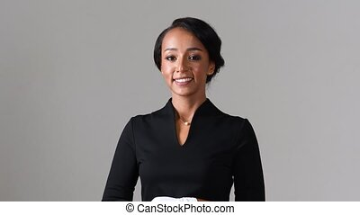 Flight attendant. Black beautiful woman wearing stewardess black dress and white gloves on gray background.