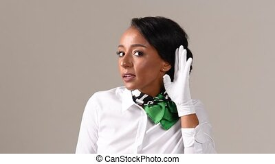 Flight attendant is actively listening. Black beautiful woman wearing stewardess uniform and white gloves on gray background.