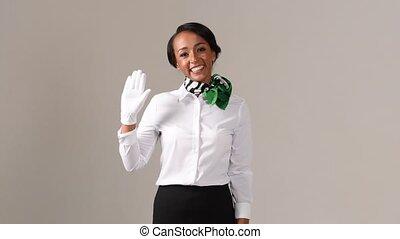Flight attendant is greeting. Black beautiful woman wearing stewardess uniform and white gloves on gray background.