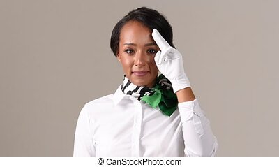 Flight attendant saluting. Black beautiful woman wearing stewardess uniform and white gloves on gray background.