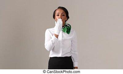 Flight attendant sending air kiss. Black beautiful woman wearing stewardess uniform and white gloves on gray background.