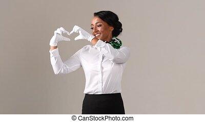 Flight attendant showing heart. Black beautiful woman wearing stewardess uniform and white gloves on gray background.