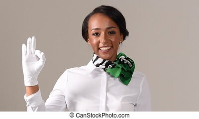 Flight attendant showing ok gesture. Black beautiful woman wearing stewardess uniform and white gloves on gray background.