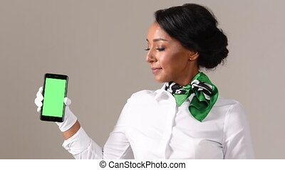 Flight attendant showing smartphone with green screen. Black beautiful woman wearing stewardess uniform and white gloves on gray background.