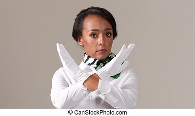 Flight attendant showing stop gesture. Black beautiful woman wearing stewardess uniform and white gloves on gray background.