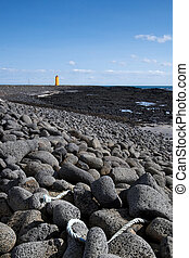 Black stone beach and the southern coast of Iceland. A yellow light tower is seen in the distance