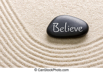 Black stone with the inscription Believe