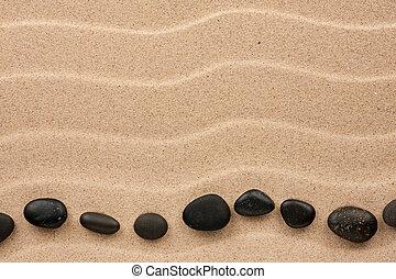 Black stones lie on the sand