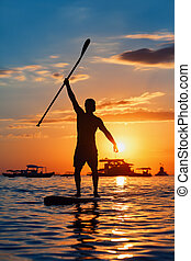 Paddle boarder. Black sunset silhouette of young sportsman paddling on stand up paddleboard. Healthy lifestyle. Water sport, SUP surfing tour in adventure camp.