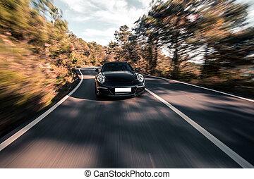 Black super model sedan car on the forest road