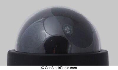 Black surveillance camera rotates, red led blink