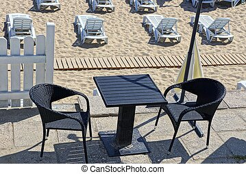 black table and chairs on the restaurant area and plastic white sunbeds in the sand on the beach