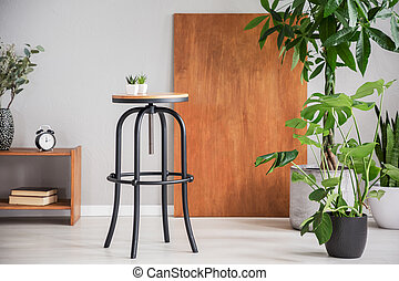 Black table between wooden cabinet and plants in grey living room interior with desk. Real photo