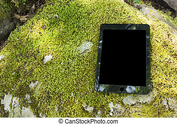 Black tablet computer on the green moss