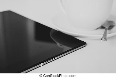 Black tablet pc with cup of coffee on the table.