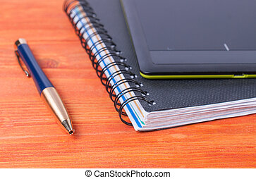 Black tablet, pen, and the diary lying on a wooden table.