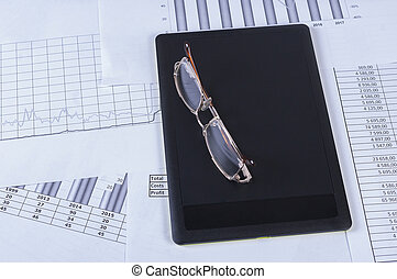 Black tablet with glasses lying on it in the financial tables and graphs