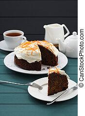 Black tea and chocolate cake with cream cheese and orange peel on dark blue background