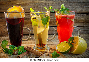 Black tea, green tea and red tea in glass cup with two slices of lemon and lime, cinnamon and herbs on rustic wood background. Top view. Black tea, milk tea, lemon tea in glass cups on a wooden table.