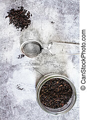 Black tea in a jar and tea infuser. Zero waste plastic free kitchen on gray background. concept sustainable lifestyle or Recycling and ecology