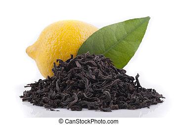 Black tea, lemon and green leaf on a white background.