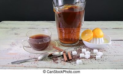 Black tea, manual squeezer with lemons. A jug of black tea and cubes of sugar.