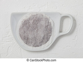 Black tea tea bag on ceramic plate with cup shape on light background.