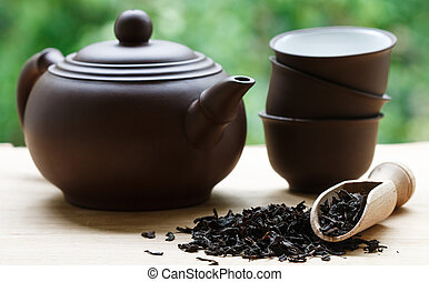 Black tea, teapot and cups on the table