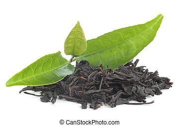 Black tea with green leavas on white background