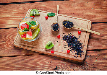 Black tea with herbs in wooden spoons on a wooden board decorated with kiwi, leaf of mint, banana, pieces of grapefruit and lime,