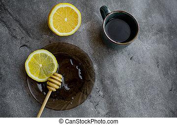black tea with honey, lemon on a gray background