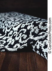 black textile with beautiful white ornament on wooden background