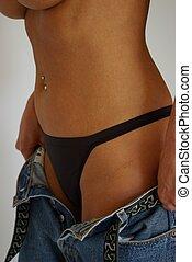 Black Thong - Female model wearing a black thong pulling on...