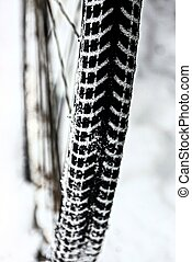 black tire on a bicycle wheel in the snow