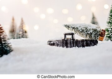 Black toy car carrying Christmas tree.
