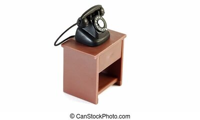 Black toy phone on small table circling isolated