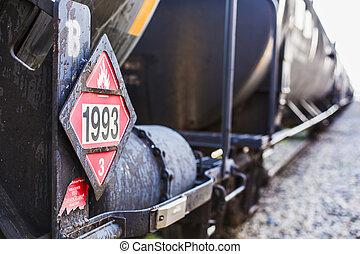 Railroad train of black tanker cars transporting crude oil on the tracks. Hazardous material sign 1993 denoting flammable liquids.