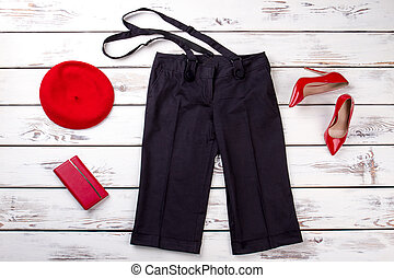 Black trousers with suspenders and red accessories.