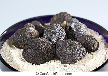 Black Truffles in rice on a white background.