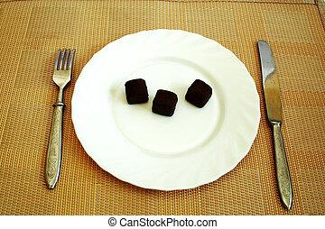 Black truffles on a white plate