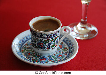 Black turkish cofee and glass water on a red cloth
